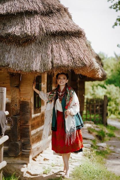 Młoda Piękność W Haftowanej Sukni Uśmiecha Się Podczas Chodzenia Darmowe Zdjęcia