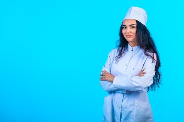 Młoda Pielęgniarka W Izolowanym Mundurze Zamyka Ramiona I Uśmiecha Się Darmowe Zdjęcia