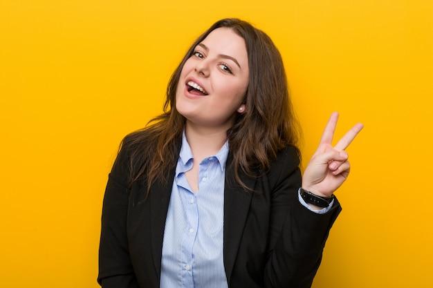 Młoda plus size kaukaska biznesowa kobieta radosna i beztroska pokazuje symbol pokoju z palcami. Premium Zdjęcia