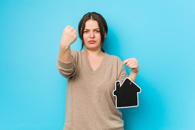 Młoda Plus Size Krągła Kobieta Trzyma Ikonę Domu Pokazując Pięść, Agresywny Wyraz Twarzy. Premium Zdjęcia
