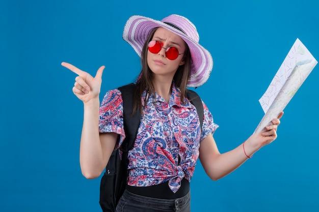 Młoda Podróżniczka Kobieta W Kapeluszu Letnim W Czerwonych Okularach Przeciwsłonecznych Trzymająca Mapę Patrząc Na Bok Z Zamyślonym Wyrazem Twarzy Wskazującym Palcem W Bok Myśląc Mając Wątpliwości Stojąc Na Niebieskim Tle Darmowe Zdjęcia