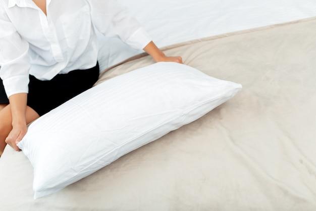 Młoda Pokojówka Robi łóżku W Pokoju Hotelowym Premium Zdjęcia
