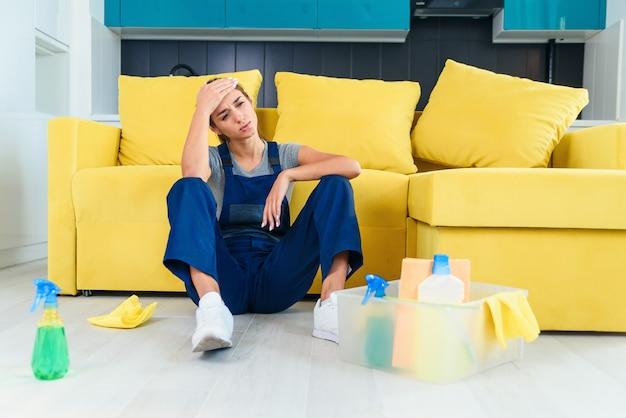 Młoda Pracownica Sprzątaczki Siedzi W Pobliżu Kanapy I Czuje Się Zmęczona Po Umyciu Podłogi W Kuchni. Premium Zdjęcia