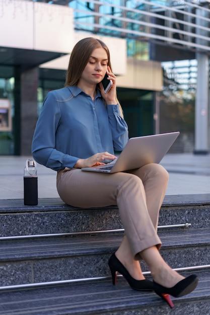 Młoda Profesjonalna Kobieta Siedzi Na Schodach Przed Szklanym Budynkiem, Trzymając Laptopa Na Kolanach I Rozmawiając Przez Telefon Komórkowy Darmowe Zdjęcia