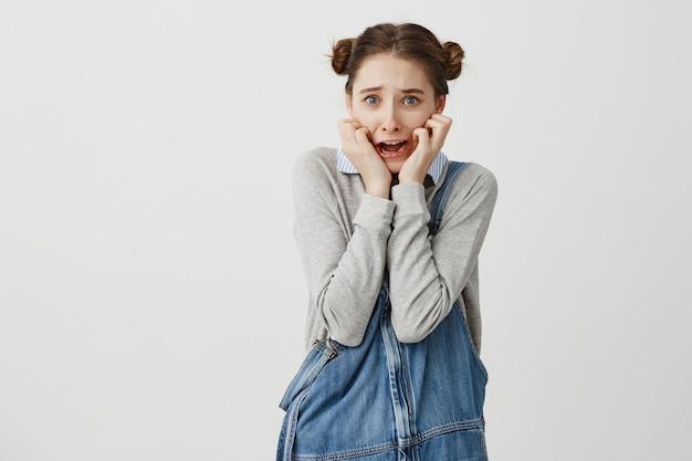 Młoda Przestraszona Kobieta W Swobodnym Ułożeniu Dłoni Na Policzkach I Krzycząca W Panice. Uczennica Jest Przerażona Po Obejrzeniu Horroru. Pojęcie Emocji Darmowe Zdjęcia