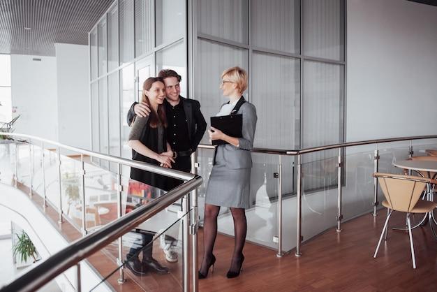Młoda Rodzina Komunikuje Się Z Urzędnikiem Przez Kobietę W Korytarzu Biurowym Premium Zdjęcia