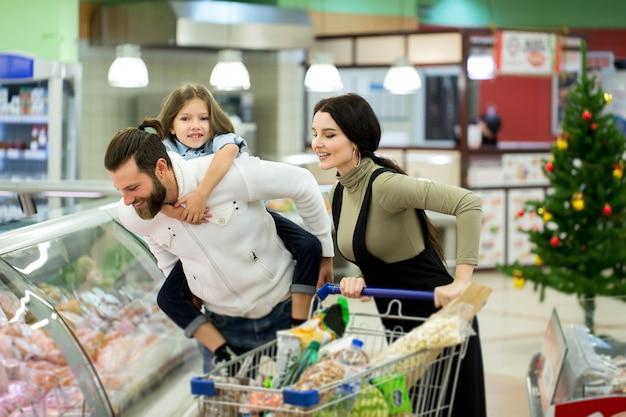Młoda Rodzina Z Małą Dziewczynką Na Zakupy W Dużym Supermarkecie. Koncepcja Nowego Roku. Premium Zdjęcia