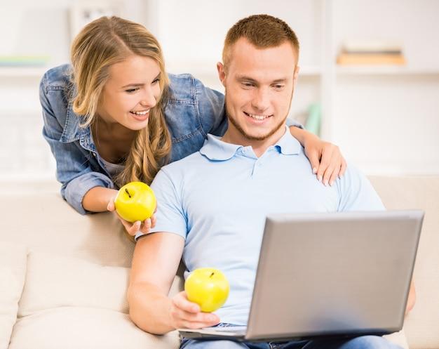 Młoda Rodzinna Para Z Zielonymi Jabłkami W Domu. Premium Zdjęcia