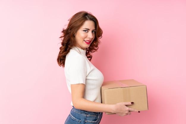 Młoda rosjanka na białym tle różowy gospodarstwa pudełko, aby przenieść go do innego miejsca Premium Zdjęcia