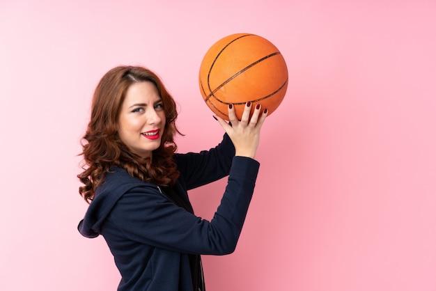 Młoda rosjanka na białym tle różowy z piłką do koszykówki Premium Zdjęcia