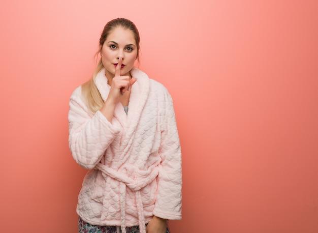 Młoda rosjanka w piżamie trzymająca w tajemnicy lub prosząca o ciszę Premium Zdjęcia