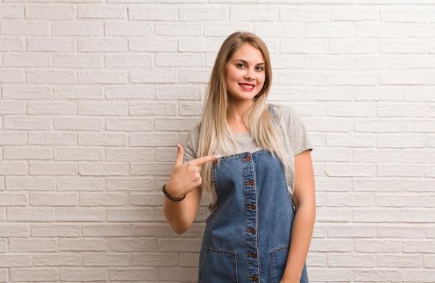 Młoda rosyjska modniś kobiety osoba wskazuje ręką do koszulowej kopii przestrzeni, dumny i ufny Premium Zdjęcia