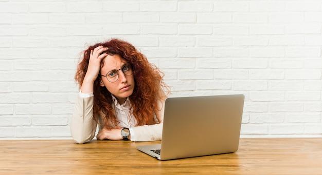 Młoda ruda kędzierzawa kobieta pracująca z laptopem jest zszokowana, przypomniała sobie ważne spotkanie Premium Zdjęcia