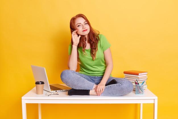 Młoda Rudowłosa Kobieta Ubrana W Zieloną Koszulkę I Dżinsy, Zadowolona Studentka Jest Zmęczona Nauką Przez Długi Czas Darmowe Zdjęcia