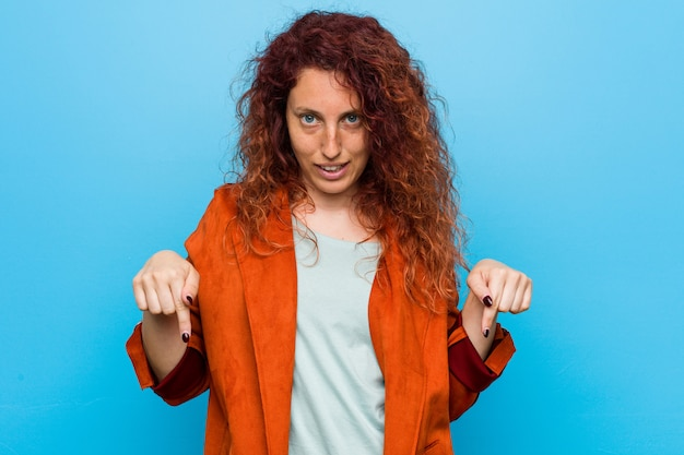 Młoda rudzielec elegancka kobieta wskazuje palcami w dół, pozytywne uczucie Premium Zdjęcia