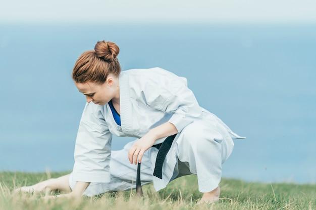 Młoda Rudzielec Karate Atlety Rozciąganie Iść Na Piechotę Na Trawie Premium Zdjęcia