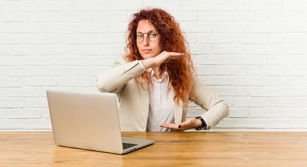 Młoda rudzielec kędzierzawa kobieta pracuje z jej laptopu mieniem coś z oba rękami Premium Zdjęcia
