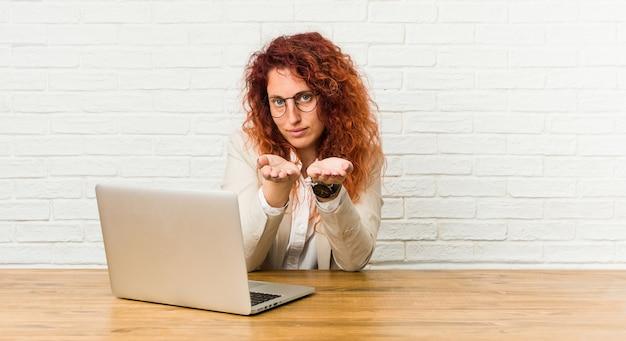 Młoda rudzielec kędzierzawa kobieta pracuje z jej laptopu mieniem coś z palmami Premium Zdjęcia
