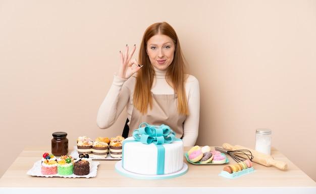 Młoda Rudzielec Kobieta Z Dużym Tortem Pokazuje Ok Znaka Z Palcami Premium Zdjęcia