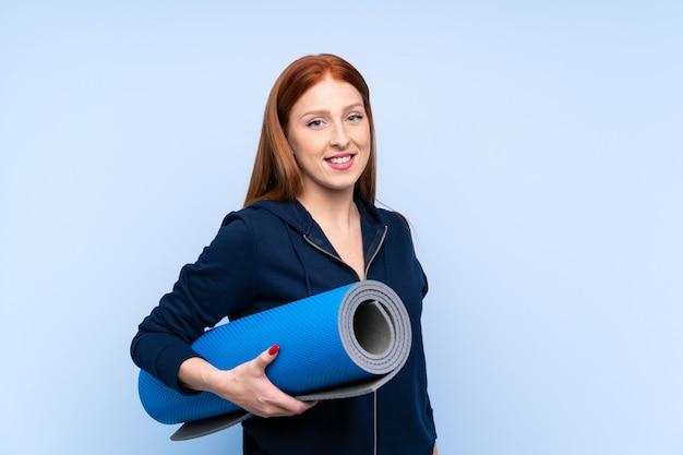 Młoda rudzielec sporta kobieta nad odosobnionym błękitnym tłem z ono uśmiecha się i matą Premium Zdjęcia