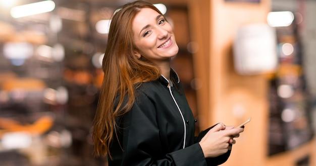Młoda rudzielec szefa kuchni kobieta wysyła wiadomość z wiszącą ozdobą w piekarni Premium Zdjęcia