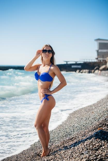 Młoda Seksowna Dziewczyna Odpoczywa Na Oceanie W Słoneczny Dzień. Rekreacja, Turystyka. Premium Zdjęcia