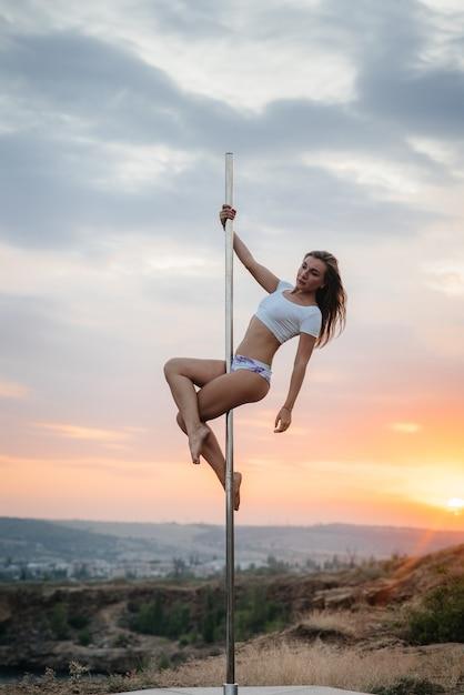 Młoda Seksowna Dziewczyna Wykonuje Niesamowite ćwiczenia Na Słupie Podczas Pięknego Zachodu Słońca. Taniec. Seksualność. Premium Zdjęcia