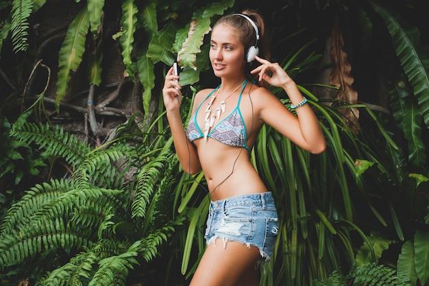 Młoda Seksowna Kobieta W Bikini I Dżinsowych Szortach, Słuchanie Muzyki Na Słuchawkach, Trzymanie Smartfona, Opalona Skóra, Chude Ciało, Zielone Tropikalne Tło, Taniec, Uśmiech Darmowe Zdjęcia