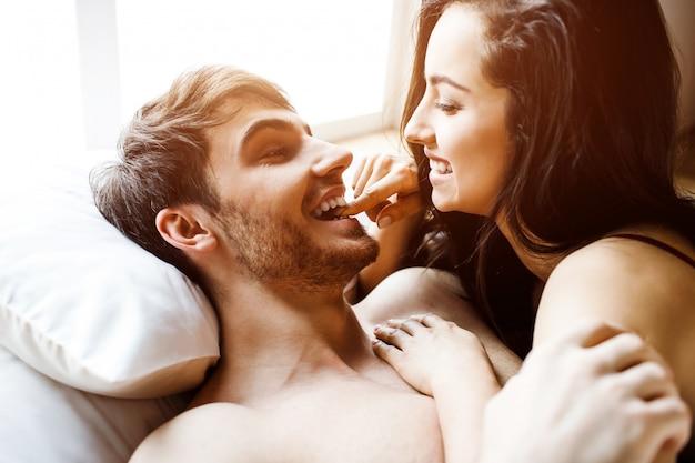 Młoda Seksowna Para Ma Intymność Na łóżku. Leżąc Razem I Uśmiechając Się. Kobieta Na Mężczyźnie. Piękni Seksowni Atrakcyjni Ludzie. światło Dzienne. Premium Zdjęcia