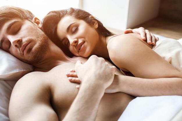 Młoda Seksowna Para Po Intymności Na łóżku. Spać I śnić Razem. Zadowoleni Młodzi Ludzie Szczęśliwi I Zachwyceni. Kobieta Objąć Mężczyznę. Trzyma Ją Za Rękę. Atrakcyjne Modele. Premium Zdjęcia