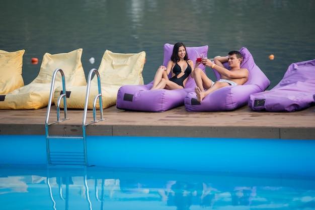 Młoda seksowna para relaksuje z napojami na amortyzujących loungers pływackim basenem i rzeką na tle Premium Zdjęcia