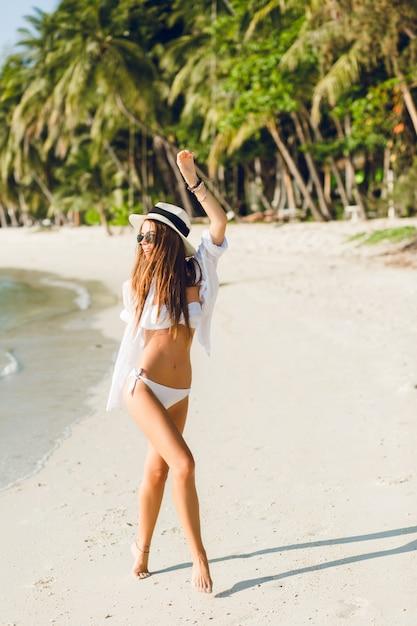 Młoda Seksowna Szczupła Dziewczyna Tańczy Na Plaży Na Sobie Białe Stroje Kąpielowe Bikini. Nosi Białą Koszulę, Ciemne Okulary Przeciwsłoneczne I Słomkowy Kapelusz. Jest Opalona I Stylowa. Darmowe Zdjęcia