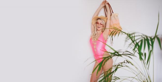 Młoda Seksowna Uśmiechnięta Szczęśliwa Blondynka W Różowym Stroju Kąpielowym, Słomkowym Kapeluszu, Okularach Przeciwsłonecznych, Podekscytowana Prezentacją Produktu. Kobieta Na Białym Tle Z Palmą Zielonymi Liśćmi. Premium Zdjęcia