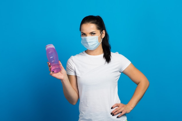 Młoda Silna Kobieta Fitness W Masce Pracy Na Białym Tle Na Tle Niebieskiej ściany Studio. Premium Zdjęcia