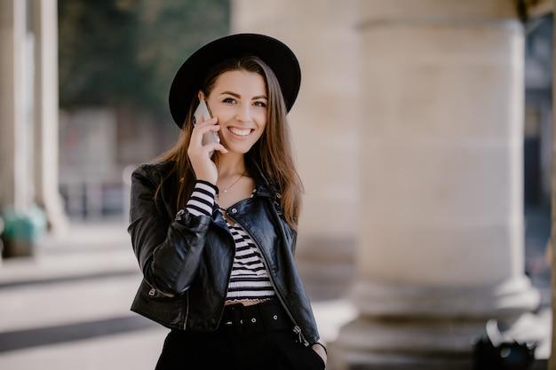 Młoda śliczna Brązowowłosa Dziewczyna W Skórzanej Kurtce, Czarnym Kapeluszu Na Miejskiej Promenadzie Prowadzi Rozmowę Telefoniczną Darmowe Zdjęcia