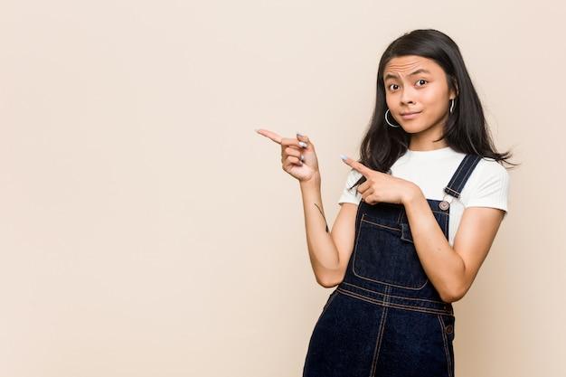 Młoda śliczna Chińska Nastolatka Młoda Blondynki Kobieta Jest Ubranym żakiet Przeciw Różowej ścianie Zszokowany Wskazuje Z Palcami Wskazującymi Do Kopii Przestrzeni. Premium Zdjęcia