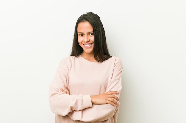 Młoda śliczna latynoska nastolatek kobieta czuje się pewnie, krzyżując ręce z determinacją. Premium Zdjęcia