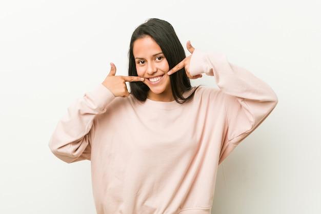 Młoda śliczna Latynoska Nastolatek Kobieta Ono Uśmiecha Się, Wskazujący Palce Przy Usta. Premium Zdjęcia