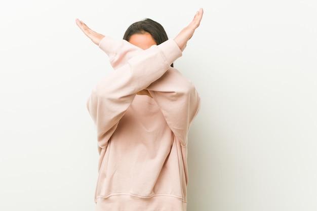 Młoda śliczna latynoska nastolatek kobieta utrzymuje dwa ręki krzyżował, zaprzeczenia pojęcie. Premium Zdjęcia