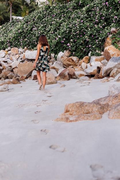 Młoda Spokojna Wytatuowana Kobieta W Letniej Tropikalnej Krótkiej Sukience Na Kamienistej Plaży Z Zielonym Krzewem I Fioletowymi Różowymi Kwiatami Darmowe Zdjęcia