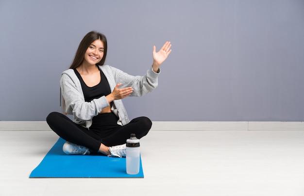 Młoda sportowa kobieta siedzi na podłodze z matą rozkładającą ręce na bok, zapraszając do siebie Premium Zdjęcia