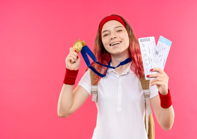 Młoda Sportowa Kobieta W Opasce Pokazując Jej Złoty Medal Trzymając Dwa Bilety Lotnicze Uśmiechając Się Z Radosną Buźką Stojącą Nad Różową ścianą Darmowe Zdjęcia