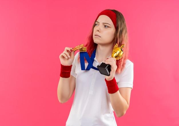 Młoda Sportowa Kobieta W Opasce Ze Złotym Medalem Na Szyi Trzyma Trofeum Patrząc Na Bok Z Poważnym Wyrazem Twarzy Stojącej Nad Różową ścianą Darmowe Zdjęcia