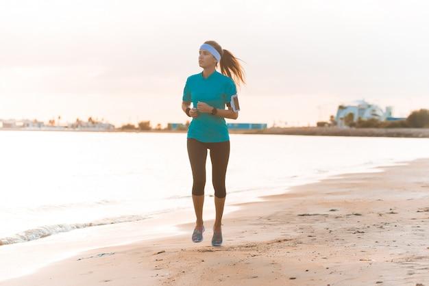 Młoda Sporty Dziewczyna Biega Na Plaży Przy Wschodem Słońca W Ranku Premium Zdjęcia