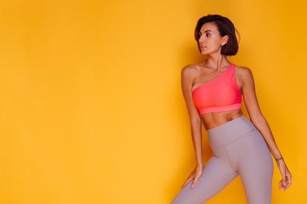 Młoda, Sprawna, Dość Silna Kobieta Ubrana W Sportowe Stroje, Stylowy Top I Legginsy, Pozuje Przed żółtą ścianą Darmowe Zdjęcia