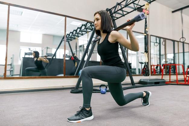 Młoda sprawności fizycznej kobieta ćwiczy w nowożytnym sporta gym. Premium Zdjęcia