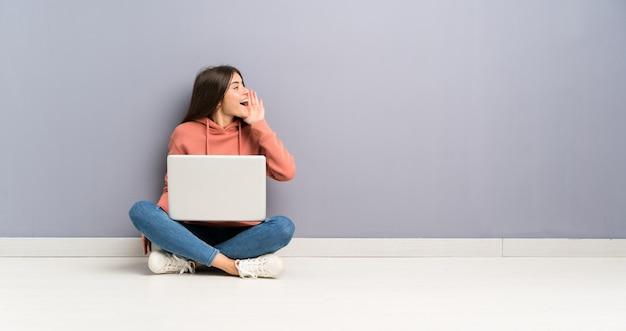 Młoda studencka dziewczyna krzyczy z usta szeroko otwarty z laptopem na podłoga Premium Zdjęcia