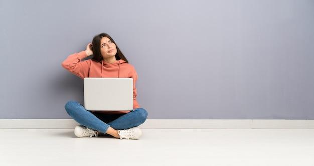 Młoda studencka dziewczyna z laptopem na podłoga ma wątpliwości i wprawiać w zakłopotanie twarz wyrażenie Premium Zdjęcia