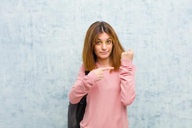 Młoda Studencka Kobieta, Patrząc Niecierpliwie I Gniewnie, Wskazując Na Zegarek, Prosząc O Punktualność, Chce Być Na ścianie Grunge Czasu Premium Zdjęcia