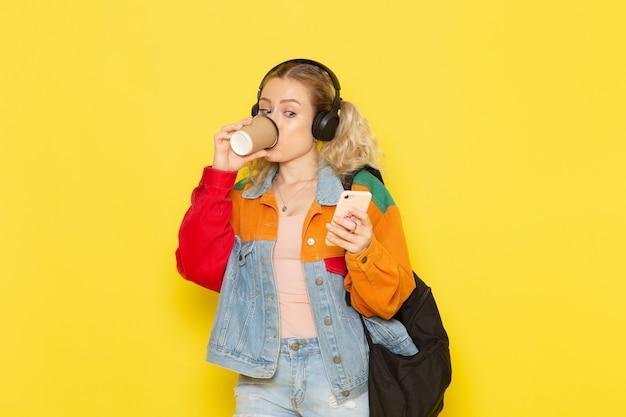 Młoda Studentka W Nowoczesne Ubrania Picia Kawy Przy Użyciu Telefonu Na żółto Darmowe Zdjęcia